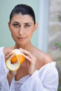 A female beauty peeling an orange